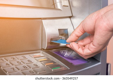 Hand inserting ATM card into bank machine to withdraw money