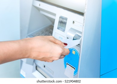 Hand inserting ATM card into bank machine for withdraw money