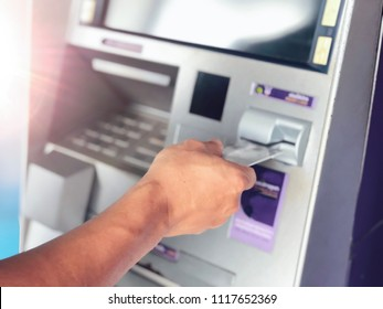 Man's hand inserting ATM credit card into bank machine to transfer money or withdraw