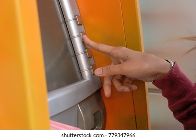 hand inserting debit card into an ATM machine. Close-up.with the credit card at the ATM . finger hand entering pressing password for withdrawing money banknotes.
