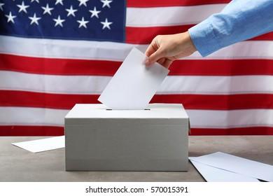 Hand inserting envelope in ballot box on USA national flag background