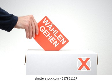 Hand inserting Envelope into Ballot Box - Vote in german language