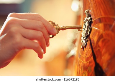Hand inserting golden key in keyhole to open lock.