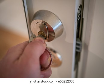 Hand inserting keys and open white door lock close up. Office, european lock style,