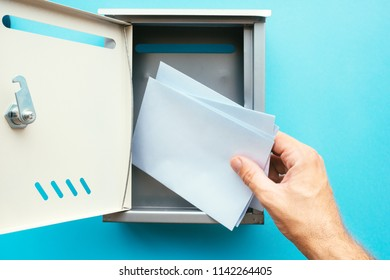 Hand inserting letter envelope into mailbox, mock up image for communication and correspondence themes