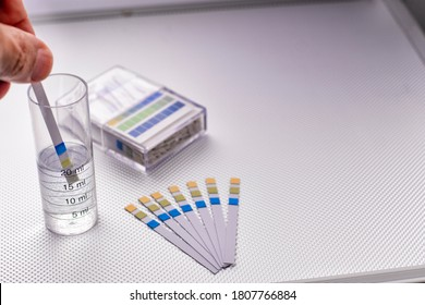 hand inserting a ph control strip into a graduated cylinder with water, selective focus