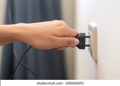instalación manual, enchufe o desenchufe de la toma de la pared ecológica; concepto de consumo, consumo o ahorro de energía