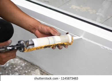 Repairman's hand installing the windows with gun silicone. closeup