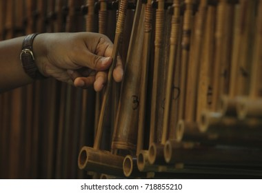 Hand with the instrument of Idiofon (Angklung) is a traditional musical instrument originating from West Jawa, Indonesia made of bamboo.