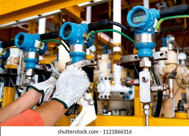Hand of instrument technician during function test or preventive maintenance pressure transmitter in oil and gas platform offshore.