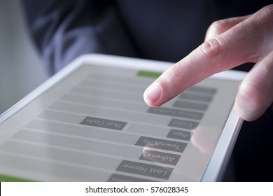 Hand interacting with digital form on the screen of a tablet. All graphics are made up.