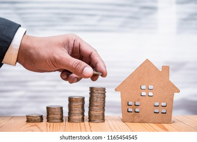 hand of investor or businessman put coin to step of coins with home model, business financial and investment concept
