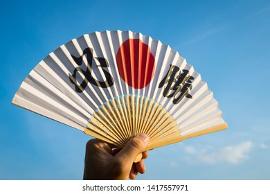 Hand of Japanese sports supporter holding a fan decorated with kanji characters spelling out hisshō, certain victory in English
