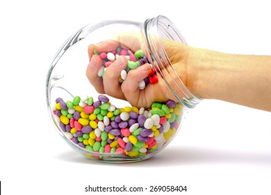 hand in a jar with colored candies isolated