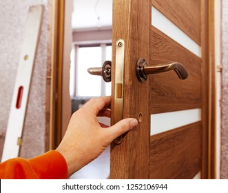 Hand of joiner who establishes a door in the room