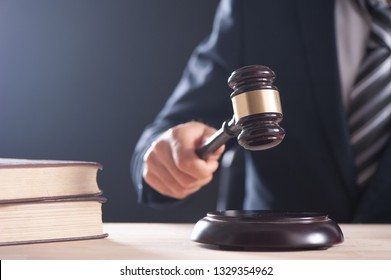 Hand of a judge holding a hammer or gavel