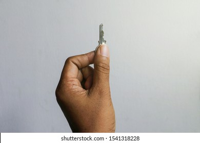 A hand keeping a key on white background