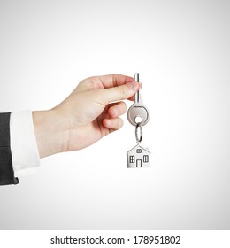 hand with key with trinket on white background