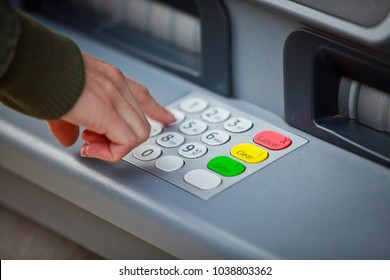 Hand keying in PIN at ATM