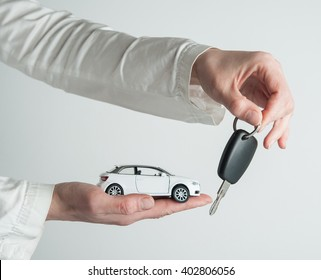 Hand with keys and car on white background. Car insurance. Automobile collision damage waiver concepts. with protective gesture and icon of car. Protection of car. Business concept.