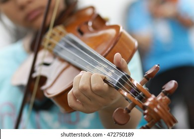 Hand of kid on the strings of a violin