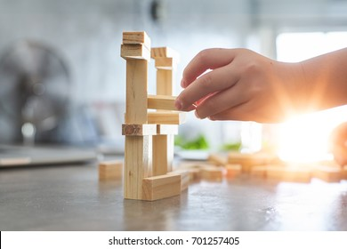 Hand of kid playing a blocks wood tower game of architectural project with sun flare and blur background .Selected focusing .