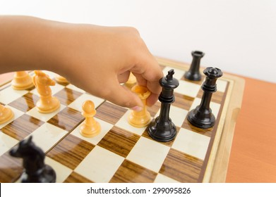 hand of a kid playing chess moving the rook to kill the king - making the checkmate