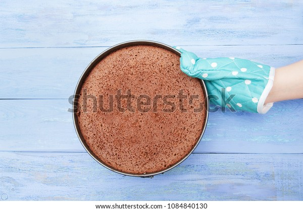 The hand in the kitchen mitten holds a shape with a baked chocolate biscuit on a blue wooden background