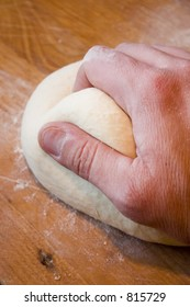 A hand kneads bread dough on the cutting board