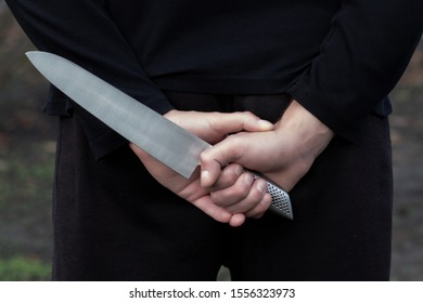 hand with a knife behind his back.