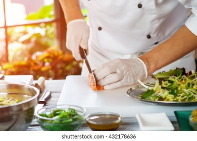 Hand with knife cuts fish. Raw fish on cooking board. Chef cutting pieces of salmon. Preparing a delicacy.