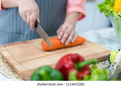 Hand with knife cutting carrot. Woman prepares food at table. Chef cooks delicious dinner. Work that requires skill.