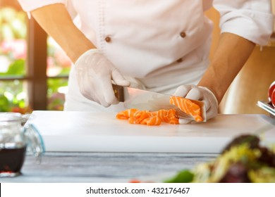 Hand with knife cutting fish. Red fish meat. Chef slices fresh salmon. Ingredient for seafood dish.