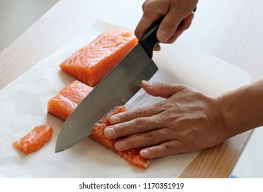 A hand with a knife cutting raw salmon.