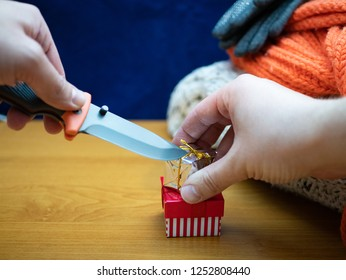 hand with knife and small gift cardbox eager inpatient man trying to unwrap unbox Christmas presents