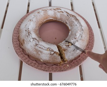 Hand with knife that cuts a slice of ciambellone dusted with velvety sugar. The cake is on pink ceramic dish resting on the outside table.