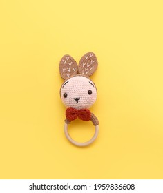 Hand knitted bunny baby rattler on yellow background
