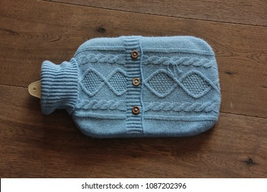 Hand Knitted Hot Water Bottle Cover on wooden background. Sud Tirol, Italy