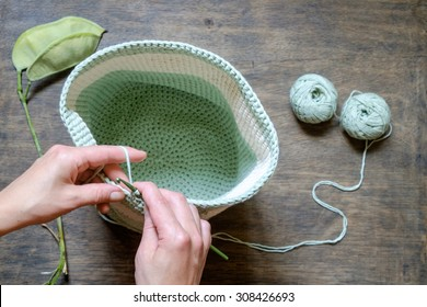 hand knitting crochet bag of green on a wooden table