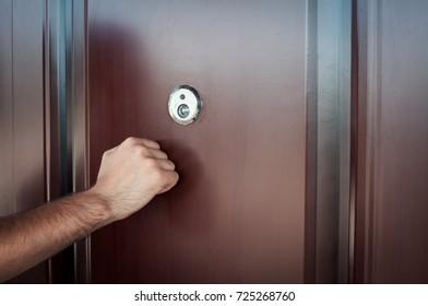 Hand knocking on door.