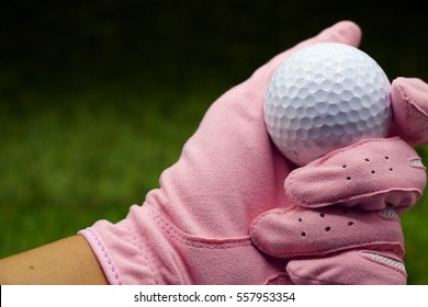 Hand of lady golfer is holding white golf ball with blurry green grass background.