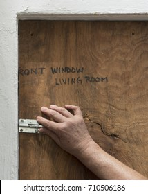 "A hand is latching a handmade plywood shutter marked ""front window living room"" over a window in preparation for a hurricane."