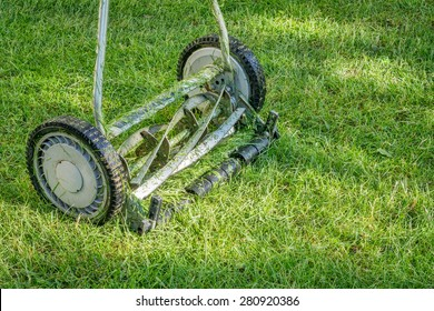 hand lawn mower close up with grass clips
