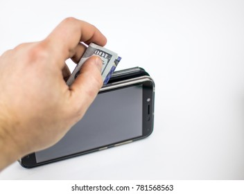 A hand lays dollars into a mobile phone against a light background. The concept of expensive conversations, money spending on communication., Electronic payments.