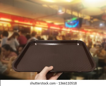 Hand lifting food tray in food court for self service food.