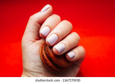Hand with light rose manicure with chokolate macarons. Isolated at bright red background.