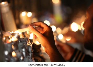 Hand lights candles on a stand with many lit burning candles