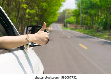 Hand like thumbs car on the road with trees along the way travel