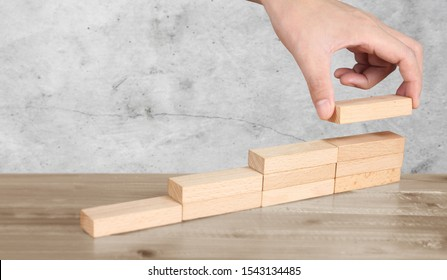 Hand liken person stepping up wood block stacking as step stair, business idea
