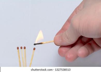 hand with a lit match ignites matches. Concept: International match day, teamwork, team, self-sacrifice, symbol.